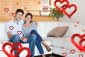 Couple sitting on a sofa against hearts