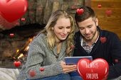 Couple using tablet PC in front of lit fireplace against always and forever
