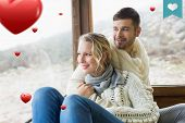 Couple in winter wear looking out through cabin window against heart label