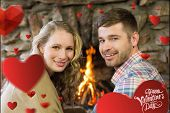 Smiling young couple in front of lit fireplace against cute valentines message
