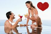 Couple having cocktails in the pool against red love hearts