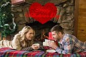 Couple with tea cups in front of lit fireplace against cute valentines message
