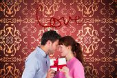 Loving couple holding a gift against elegant patterned wallpaper in red and gold