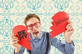 Geeky hipster holding a broken heart against elegant patterned wallpaper in blue and cream