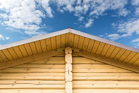 pic of gable-roof  - Wooden roof gable with log wall against cloudy sky - JPG
