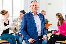 picture of professor  - University college professor standing in class room - JPG