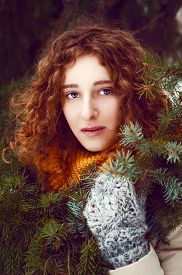 foto of auburn  - Attractive young woman with curly auburn hair near pine tree with yellow snood and mittens - JPG