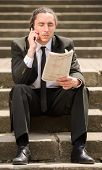 stock photo of unemployed people  - Man in suit sitting at stairs with newspaper - JPG