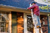 stock photo of gutter  - Man Cleaning Gutters on a Ladder Against a Brick House - JPG