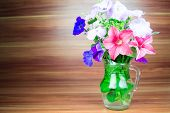 foto of petunia  - Colorful petunia blooms in a glass pitcher - JPG