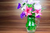 picture of petunia  - Colorful petunia blooms in a glass pitcher - JPG