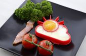 stock photo of black-cherry  - Bright happy breakfast with sunny egg bacon tree with parsley leaves and cherry tomato flowers on black square plate on white wood table - JPG