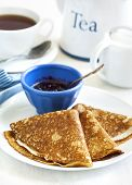 image of crepes  - Homemade Crepes Folded In Triangles With Black Currant Jam And Cup Of Tea  - JPG
