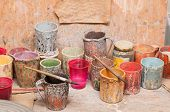 foto of pottery  - Work table of a pottery decorator of Caltagirone with different color containers and paintbrushes - JPG