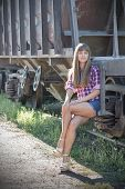 image of railroad car  - Skinny girl is sitting on the steps of the old railroad freight car - JPG