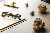 stock photo of stress-ball  - Crumpled paper balls with eye glasses and notebook on wood desk with soft light - JPG
