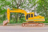 pic of backhoe  - Single backhoe color yellow on the road - JPG