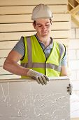 stock photo of insulator  - Builder Fitting Insulation Boards Into Roof Of New Home - JPG