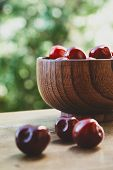 image of berries  - Vertical photo of cherry berries in the wooden bowl on the wooden table on the green bokeh background with three berries out of the bowl - JPG