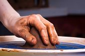 image of molding clay  - hand with clay on pottery wheel - JPG
