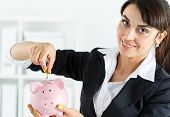 foto of coins  - Happy beautiful woman putting pin money coins into pink piggybank slot - JPG