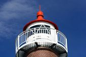 Closeup Of The Top Of A Lighthouse Against Blue Sky.
