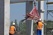 image of slab  - Construction worker navigating with concrete slab lifted by crane at building site - JPG