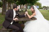 stock photo of wrestling  - Young happy newly wed couple fighting in arm wrestling - JPG