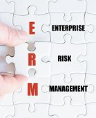 stock photo of enterprise  - Hand of a business man completing the puzzle with the last missing piece - JPG
