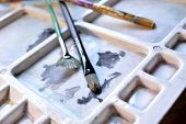 pic of paint palette  - Three paintbrushes on an artist