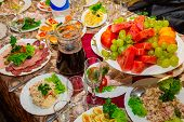 foto of crockery  - Festive table with fruit salads and cold meats - JPG
