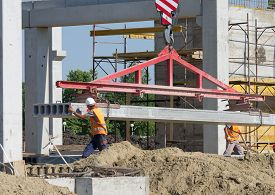 foto of slab  - Construction worker navigating with concrete slab lifted by crane at building site - JPG