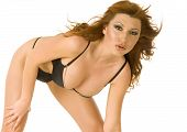 picture of crotch  - A beautiful redheaded woman bends down in a black bikini showing off her cleavage - JPG