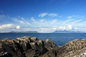 stock photo of eigg  - Summer skies over the Isles of Eigg and Rum from Mallaig - JPG