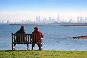 Постер, плакат: Мужчина и женщина на скамейке clifftop любоваться видом на залив на город небоскребов Мельбурн пров