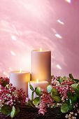 Christmas candles in a pastel floral wreath.  Background is natural light reflected from bevelled gl