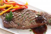 Asado tira o porterhouse alimentados con grano solomillo, con colores vegetales y una salsa de cebolla.