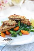Weiner schnitzel with vegetables and little orange tomatoes.