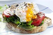 Poached egg on sourdough toast, with grilled tomatoes, mushrooms and salad leaves.  A healthy, delic