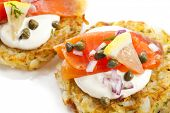 Smoked salmon and sour cream on potato latkes or rostis.
