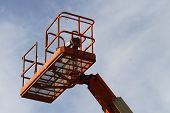 pic of cherry-picker  - Orange cherry picker crane against a blue sky - JPG