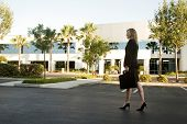 Business Woman Walking Through Parking Lot Carrying Briefcase