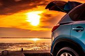 Blue Compact Suv Car With Sport And Modern Design Parked On Concrete Road By The Sea At Sunset. Envi poster