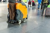 Man Driving Professional Floor Cleaning Machine At Airport Or Railway Station.  Floor Care And Clean poster