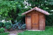 stock photo of wooden shack  - Wooden garden tool shed in a beautiful park - JPG