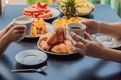 Happy Family Having Breakfast On The Balcony. Breakfast Table With Coffee Fruit And Bread Croisant O poster