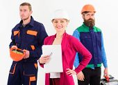 Woman In Hard Hat With Smiling Face Stand In Front Of Male Builders In Uniform, Defocused. Team Of B poster