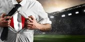 Peru soccer or football supporter showing flag under his business shirt on stadium. poster