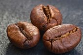 three coffeebeans on black stone
