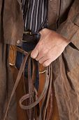 stock photo of bridle  - A cowboy holding on to his belt while he holds on to his bridle - JPG